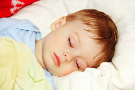 ittle baby asleep in bed, his head on the pillow close-up. Фото со стока