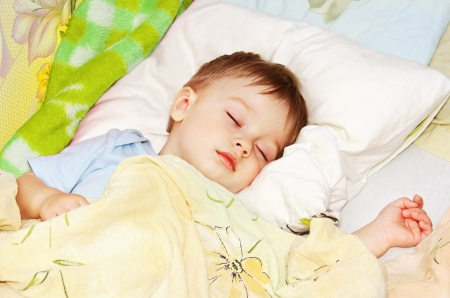 ittle baby asleep in bed, his head on the pillow close-up. Standard-Bild