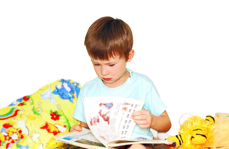 preschool boy reading a book, a photo on a white background.
