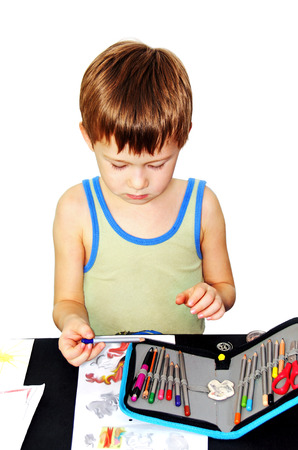 boy draws a picture of pencils on paper, white background.