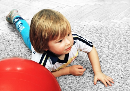 little boy playing with a big red ball in the house.