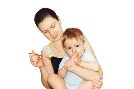 young mother holds her baby child in her arms and fed him with a spoon, photo on the white background