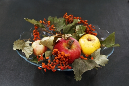 apples, dried leaves and rowan berries in a glass vase standing on the dark surface of the table