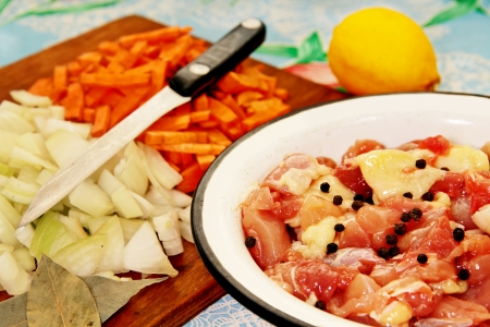 cut into pieces of chicken in a bowl, finely diced vegetables and lemon on the kitchen table
