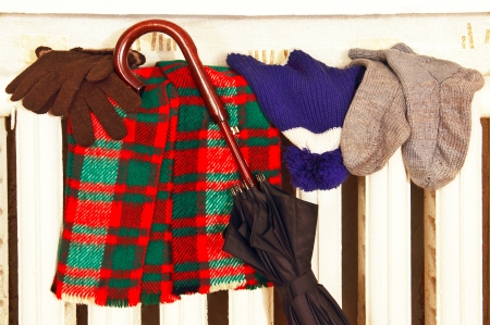 winter clothes and a large umbrella drying on a radiator room