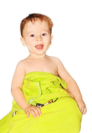 cheerful child after bathing, wrapped in a green towel, white background.