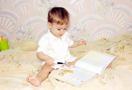little boy flips through a large book sitting on the couch.