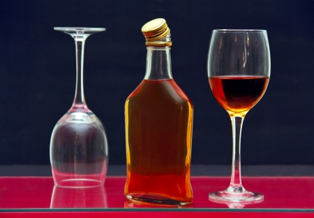one bottle and two glasses of alcohol on the glass surface of the table.  Фото со стока