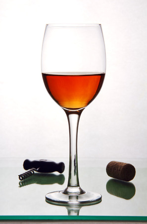one glass of alcohol, cork and corkscrew on a glass table top. Фото со стока