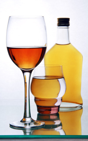 one bottle and two glasses of alcohol on the glass surface of the table.