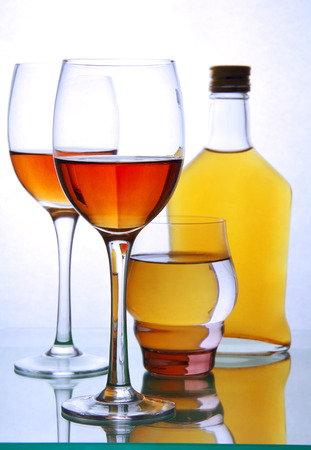 one bottle and three glasses of alcohol on the glass surface of the table. Фото со стока