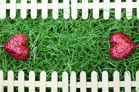 Red hearts on green grass background and fence for Valentines Day Stock Photo