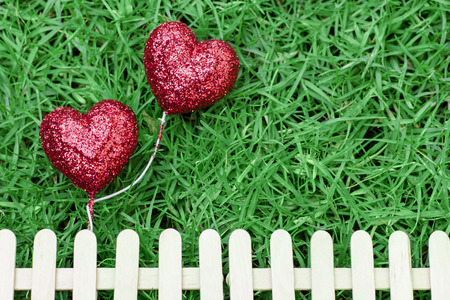 Glitter red hearts on green grass background and fence