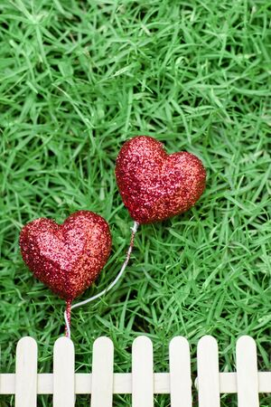 ramantic: Glitter red hearts on green grass background and fence
