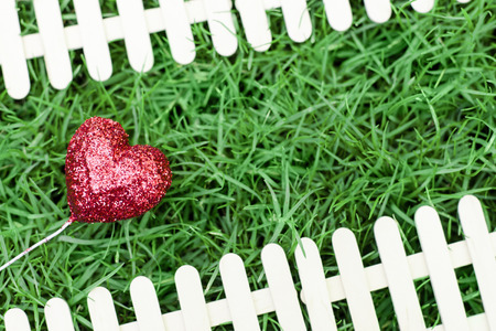 Glitter red heart on green grass background and fence