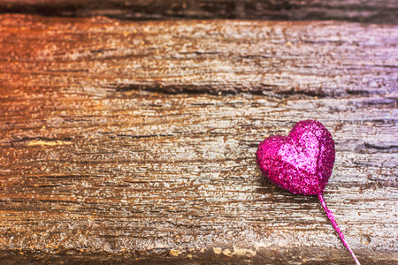Sparkling pink heart on gradient wooden background