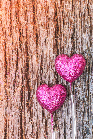 Sparkling pink hearts on gradient wooden background