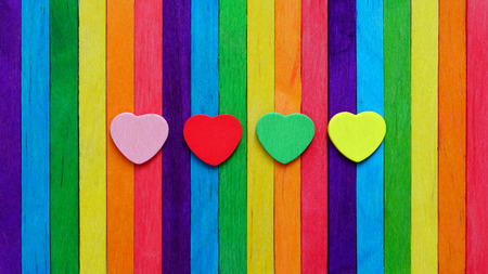 Four hearts in multiple colors on colorful ice-cream sticks line up as rainbow flag. LGBT love concept.