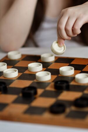 Little girl plays checkers in white clothes on a light background