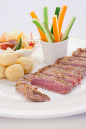 sirloin grilled serve with somtum, sticky rice ball and vegetales in thai style