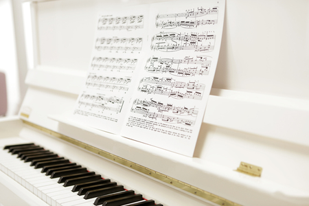 musical score: music notes sheet put on a white beauty piano