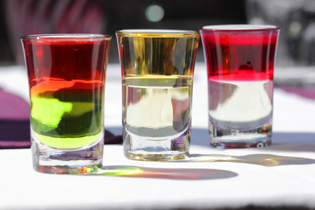 shooters: three shot of layer cocktail, vodka, curacao, tequila, grenadine, peppermint schnapps, Stock Photo
