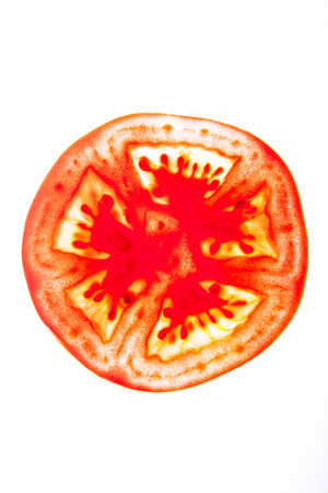 a piece of tomato sliced in bright white background seem transparent