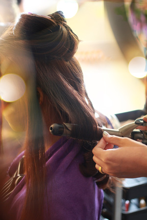 stylist rolling customer's hair with curling iron Editorial