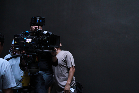 A cameraman with his team working in studio for shooting a movie Фото со стока