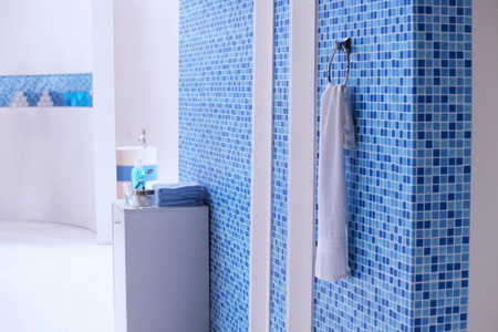 a white towel hanging on the blue mosaic tile wall in the bathroom setup for shooting movie