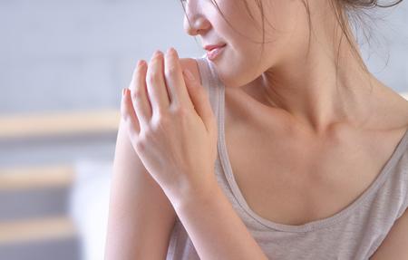 jonge vrouw die haar schouder aanraakt en trots is op haar gezonde huid na het aanbrengen van de crème