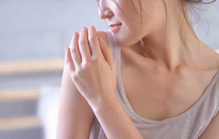 junge Frau, die ihre Schulter berührt und stolz mit ihrer gesunden Haut ist, nachdem sie die Creme aufgetragen hat