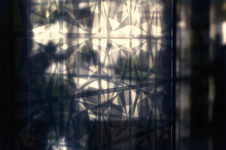 a glass wall is refrected the graphic pattern ornament with outside lighting Reklamní fotografie