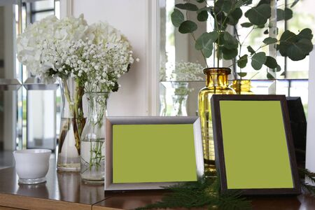 two photo frames put on a desk surround with white flower vases and leave for decoration