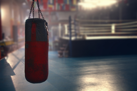 a red sanbag is hanging in front of the boxing ring in a gym for shooting a movie
