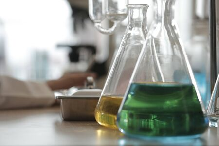 green and yellow solutions in science flask put in a laboratory prepared for test 스톡 콘텐츠