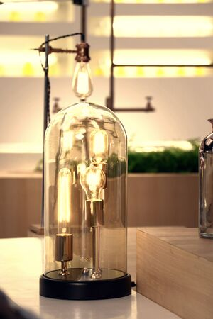 a table electric lamp in vintage design consist of many retro light bulbs in one cover