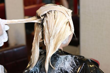 light color hair are pull for applying some color bleaching cream in salon