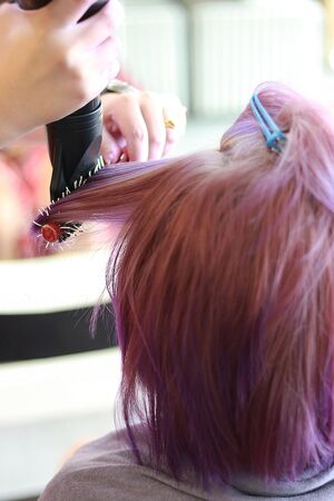 the hairdresser use a roll hairbrush and hair dryer blow on the purple hair in salon