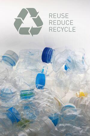 Ein Symbol und die Wiederverwendung von Wörtern reduzieren das Recycling, das über viele zerdrückte Plastikflaschen in weißem Hintergrund gelegt wird