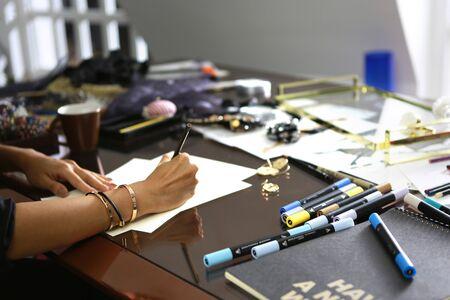 fashion designer is working on her messy desk in studio