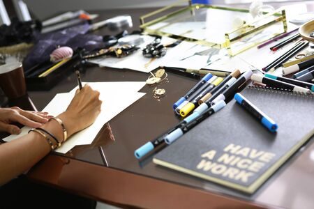 fashion designer is sketching her work on messy desk