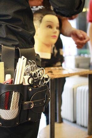 variety of scissors and combs put in a hairdressor belt student use for work with mannequin
