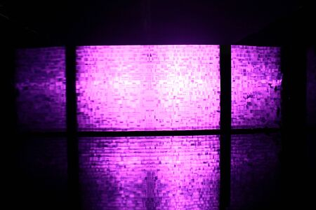 a transparent plastic partiontion consist of many block shape hit by purple light in behind