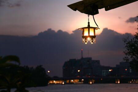 a vintage lantern hanging with roof of old house by riverside againt with sunset in twilight rustic scene