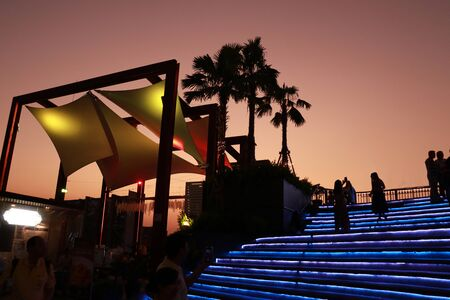 the yellow tropical canvas roof againt with orange sky but the blue lighting stair is difference