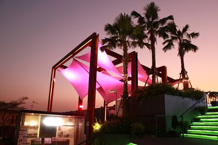 a modern tropical roof structure with palm trees and stairway against with purple twilight sky 스톡 콘텐츠