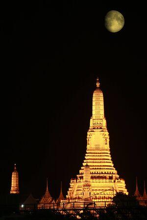 Wat Arun pagoda a most famous landmark of Bangkok is brightly under the moon