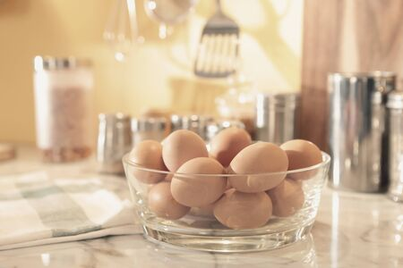 a lot of eggs are contained in a big glass bowl and put on the kitchen counter