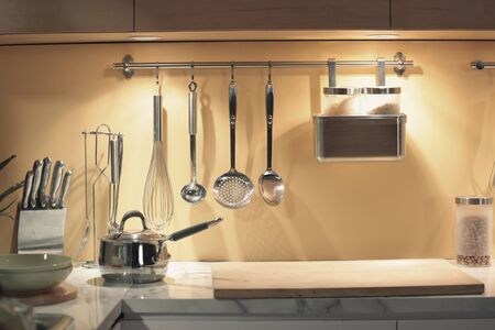 a lot of kitchenwares hanging on the wall and put on the kitchen counter